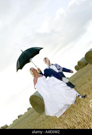 Bride & Groom walking through fields on hay bales - Stock Photo