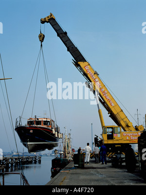Lifeboat being lifted by a mobile hydraulic crane, Grimsby, Humberside, North Lincolnshire, England, UK. - Stock Photo