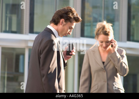 MR Business man and woman on their way telephoning and speaking something to a voice reorder - Stock Photo