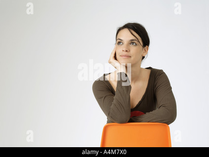 Young woman sitting backwards on chair, portrait - Stock Photo