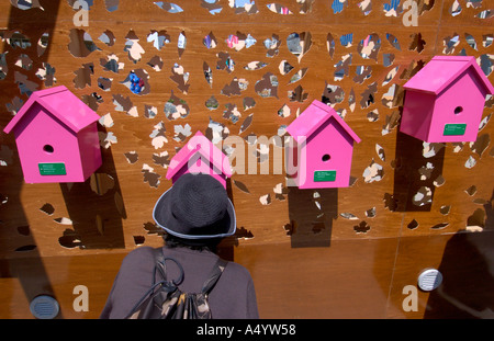 Visitors to the UK Pavilion look at photographs of the UK inside birdhouses World Expo 2005 Aichi Japan - Stock Photo