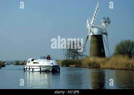 Broads cruiser going past Turf Fen Windpump on the River Ant in Norfolk - Stock Photo