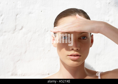 A young woman shielding herself from the sun looking at camera - Stock Photo