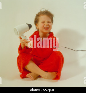 child holding electric hairdryer. Photo by Willy Matheisl - Stock Photo
