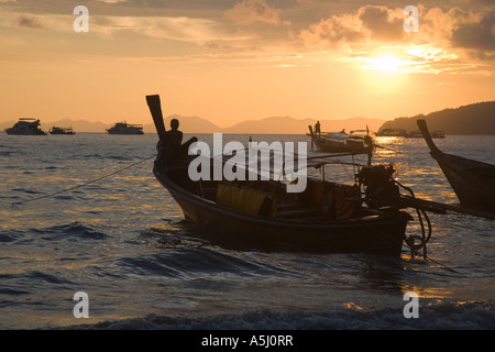 Long tail boats on Railay or Railey beach lagoon, Krabi Province Andaman Sea, Thailand, at sunset. - Stock Photo