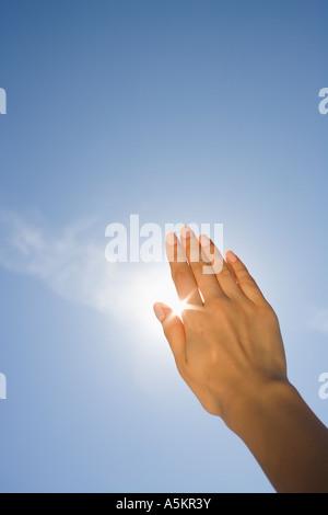 Close up of woman s hand blocking sun - Stock Photo