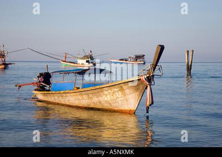 Longtailed fishermans Boat moored on still Andaman sea Krabi Beach Resort Krabi Province Southern Thailand - Stock Photo