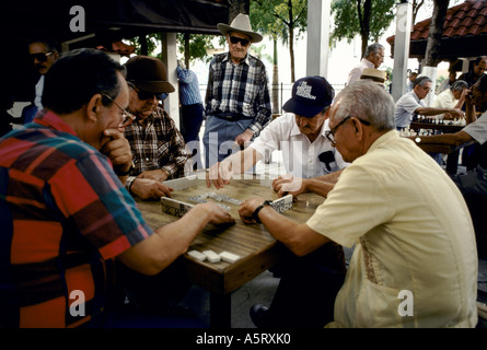 CUBAN EXILE COMMUNITY MIAMI,  OLD MEMBERS OF THE COMMUNITY PLAY DOMINOS WHILE SMOKING CIGARS - Stock Photo