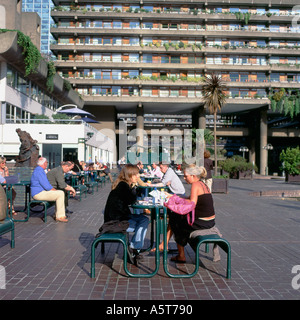 People sitting at tables eating and drinking at the outdoor cafe on the lakeside terrace in summer at the Barbican - Stock Photo