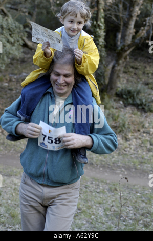 Man carrying a little girl on his shoulder - Stock Photo