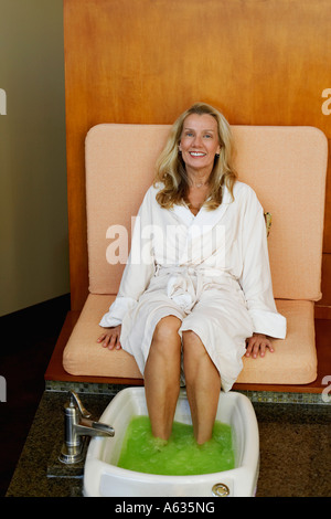 Portrait of a mature woman getting pedicure - Stock Photo