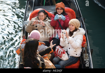Japanese visitors to Venice Italy use their digital cameras as they take a gondola ride around the city - Stock Photo