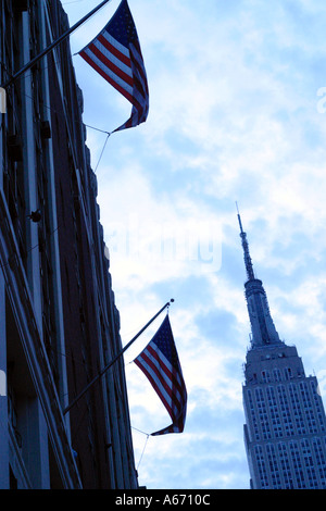 A view of the Empire State Building with American flags flags in the foreground in ew York in the United States - Stock Photo