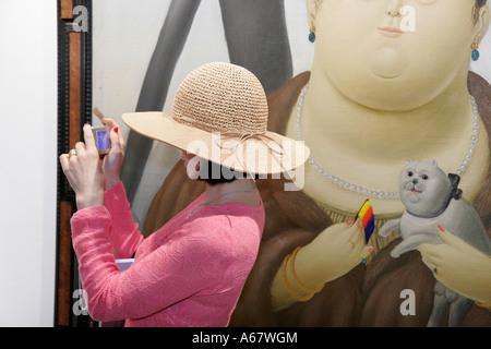 Miami Beach Florida Convention Center Arte Americas Latin American Art Fair woman camera fashion hat painting - Stock Photo