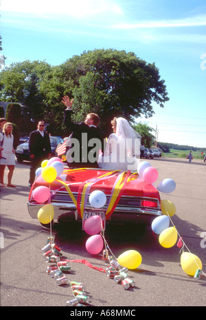 Wedding couple leaving church in red convertible age 25. Battle Lake Minnesota USA - Stock Photo