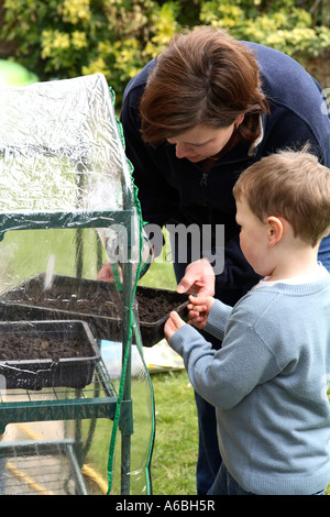 Mother helping her young son place planted seed trays into small plastic greenhouse for germination in early spring - Stock Photo
