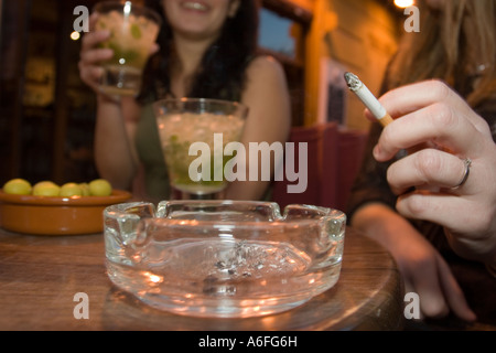 Two women sat drinking and smoking. - Stock Photo