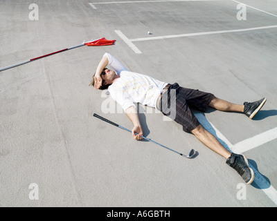 Golfer lying in car park - Stock Photo