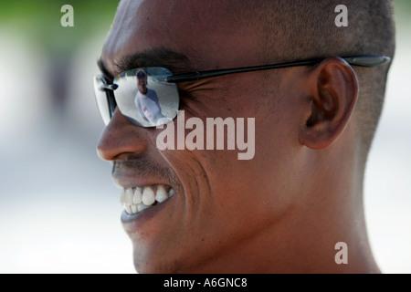 Snorkel boat skipper talks to friend reflected in sunglasses Perhentian Kecil Malaysia - Stock Photo