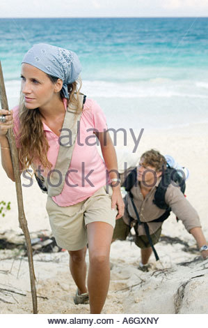 Couple walking up sand dune - Stock Photo