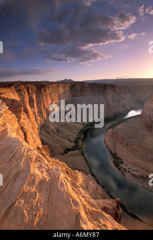 Sunset light on sheer sandstone cliffs above the Colorado River Canyon at Horseshoe Bend near Page Arizona - Stock Photo