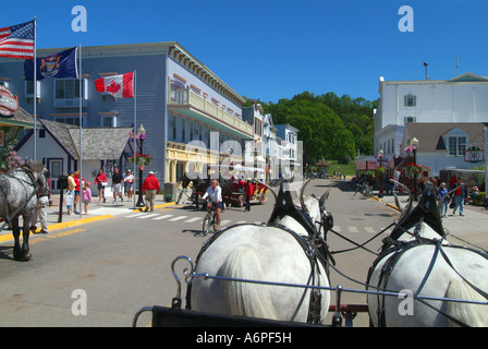 USA Michigan Lake Huron Mackinac Island downtown Main Street horse and carriages - Stock Photo