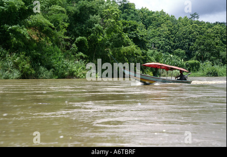 Long-tail boat travelling on Mae Nam Kok river between Tha Ton and Chiang Rai North Thailand - Stock Photo