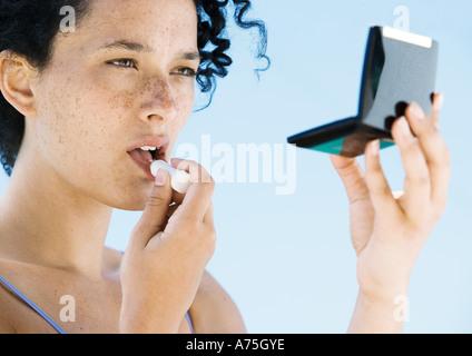 Young woman applying lipstick - Stock Photo