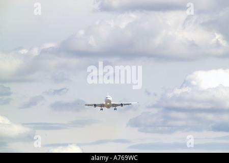 A passenger jet aircraft coming in to land viewed from the front with a cloudy sky. - Stock Photo