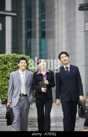 Three young executives walking side by side - Stock Photo