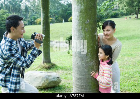 Man videotaping wife and daughter in park - Stock Photo