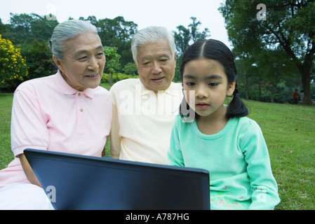Girl and grandparents using laptop - Stock Photo