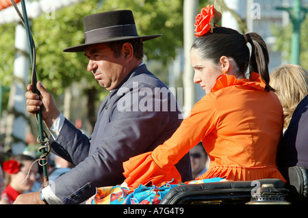 Carriage driver with a whip  and a girl in an orange flamenco dress at Seville's April Fair - Feria de Abril - Stock Photo