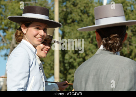 Portrait of girls in traditional dress laughing and talking as the ride through Seville's April  Fair - Feria de - Stock Photo