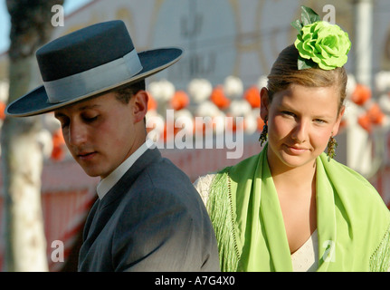 Young man with a girl in  traditional dress pillion behind him ride through Seville's April Fair - Feria de Abril - Stock Photo