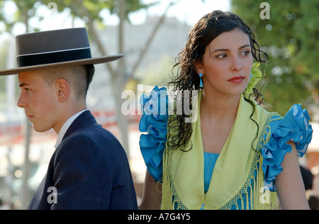 Girl in turquoise and green  flamenco dress and young man  in traditional costume ride through Seville's April Fair - Stock Photo