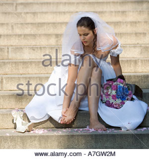 A bride sitting outside the church massaging her feet - Stock Photo