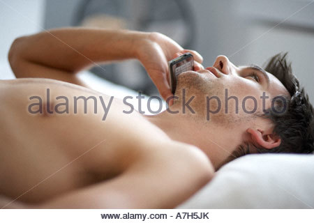 Young man laying on a bed talking on a mobile phone, close-up - Stock Photo