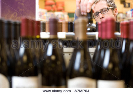 Man shopping for wine in supermarket choosing bottle from shelf focus on background - Stock Photo