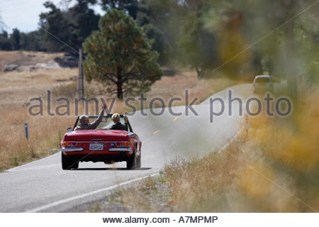 Senior couple driving along country road in red convertible car rear view - Stock Photo