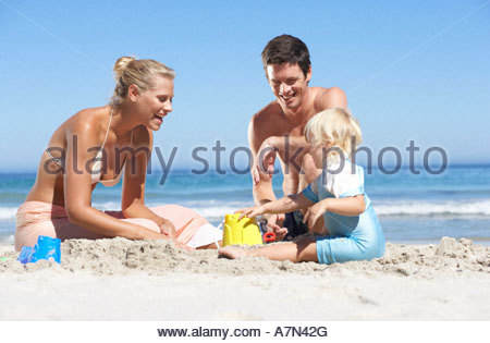 Two generation family building sandcastles on sandy beach smiling - Stock Photo