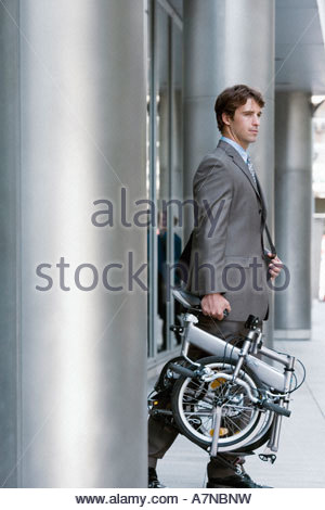 Businessman leaving office building carrying folding commuter bicycle side view - Stock Photo