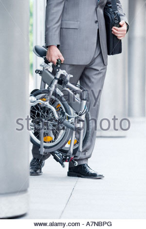 Businessman leaving office building carrying folding commuter bicycle side view low section - Stock Photo