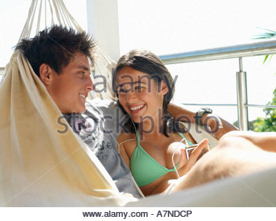 Teenage couple 15 17 relaxing in hammock on balcony smiling close up - Stock Photo