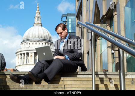 London England United Kingdom UK City gent using laptop computer in shadow of St Pauls Cathedral - Stock Photo