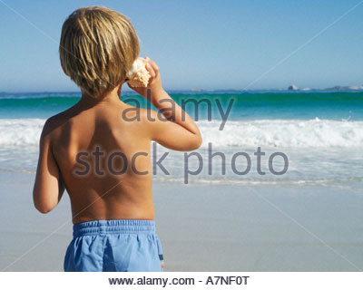 Blonde boy 5 7 standing on beach listening to sea shell looking at horizon over sea rear view - Stock Photo