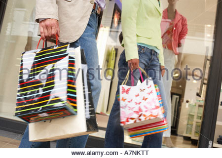 Couple with shopping bags walking past window display in clothes shop low section tilt - Stock Photo