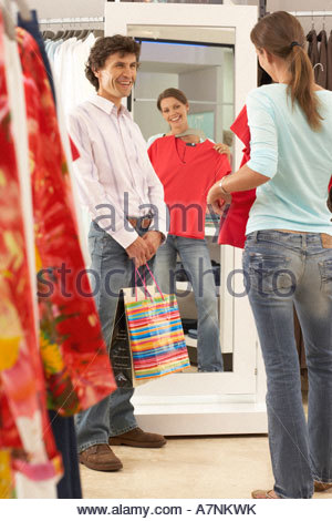 Woman trying on red top in clothes shop looking at reflection in mirror boyfriend looking on smiling rear view - Stock Photo