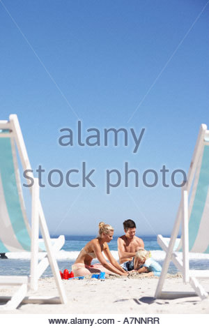 Young family building sandcastles on sandy beach deckchairs in foreground - Stock Photo