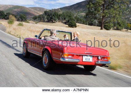 Mature couple driving in red convertible car along country road woman taking photograph rear view - Stock Photo